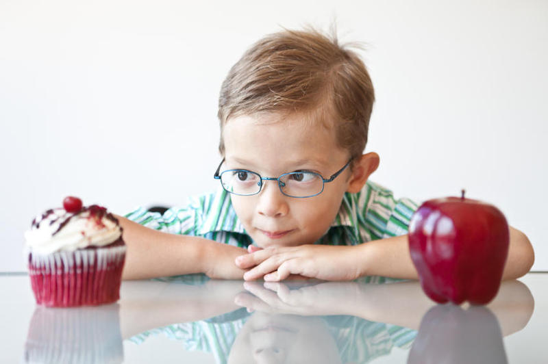 a boy making a choice between an apple or cupcake