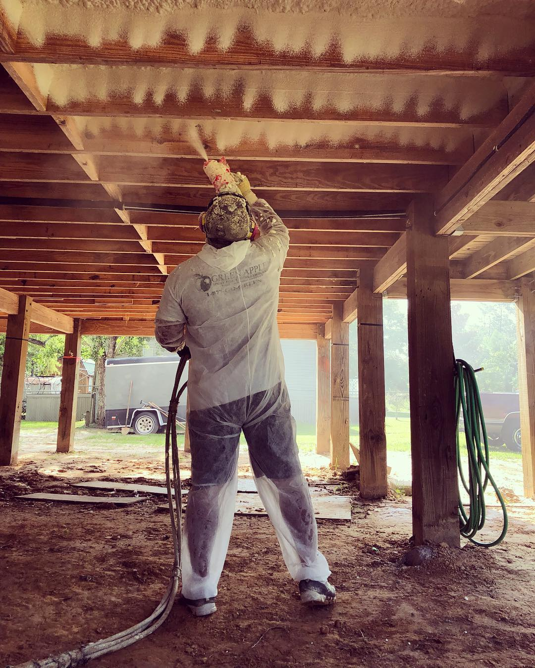 spraying closed cell spray foam under a new construction home